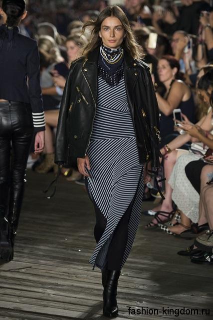 Короткая кожаная куртка черного цвета, свободного кроя в тандеме с длинным черно-белым платьем от Tommy Hilfiger.