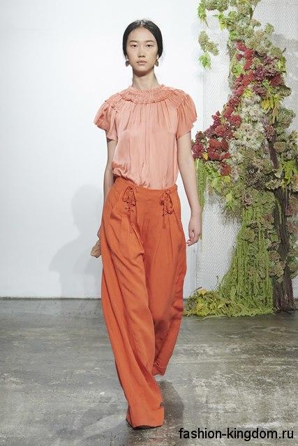 Широкие брюки кирпичного цвета сочетаются с блузой персикового оттенка с короткими рукавами от Ulla Johnson.