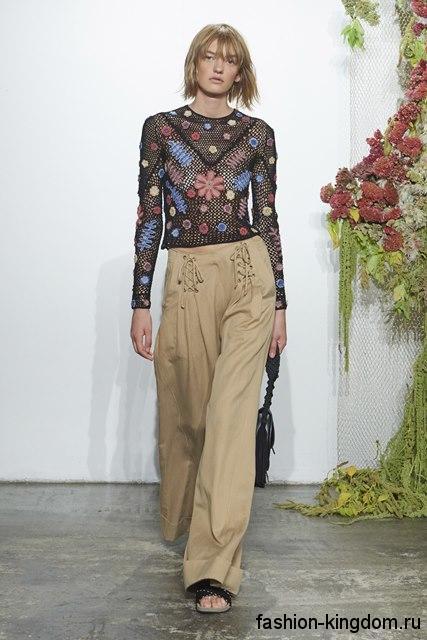 Ажурная блузка черного тона с цветными аппликациями и длинными рукавами в тандеме с широкими брюками от Ulla Johnson.