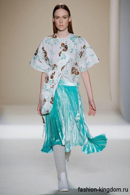 Асимметричная белая блузка с цветным принтом и короткими рукавами в сочетании с бирюзовой юбкой-плиссе от Victoria Beckham.