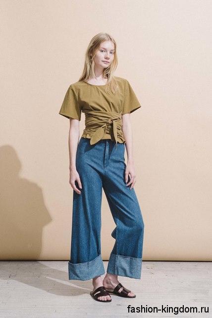 Короткая блузка горчичного цвета, с короткими рукавами и длинным поясом в тандеме с широкими джинсами от Zac Posen.