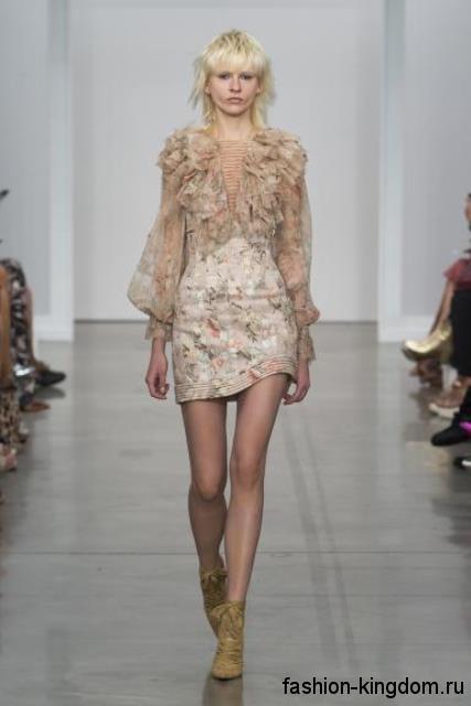 Шифоновая блузка бежевого цвета с оборками и длинными рукавами в тандеме с юбкой-мини с высокой талией от Zimmermann.