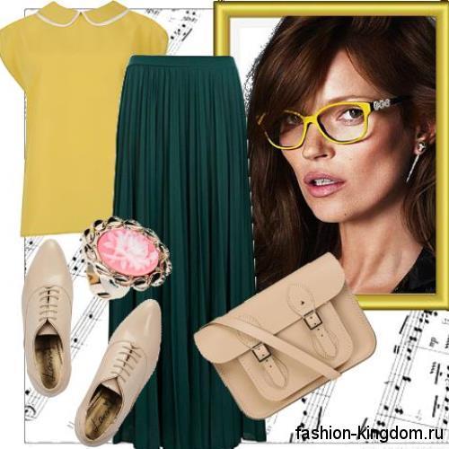 Желтая блузка с короткими рукавами, прямого фасона сочетается с длинной юбкой темно-зеленого цвета.