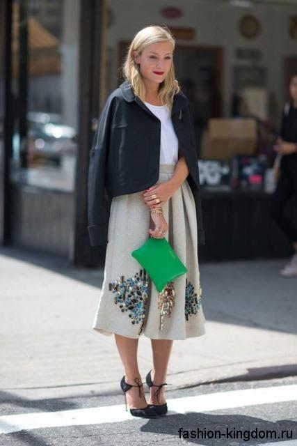 Бежевая юбка-миди с высокой талией, декорированная цветными камнями, сочетается с короткой черной курткой.