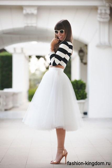 Пышная юбка-миди белого цвета, длиной до колен в сочетании с топом черно-белого тона в полоску.