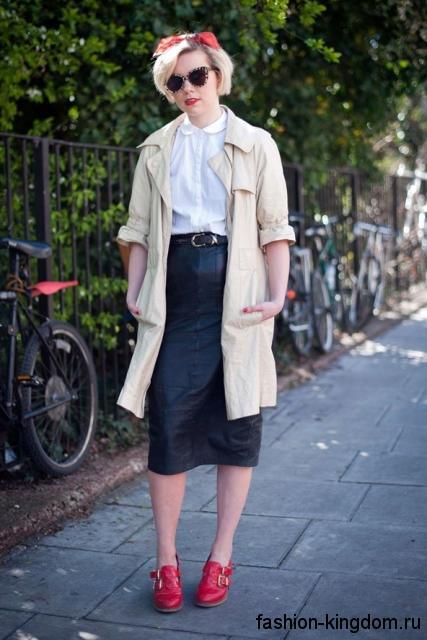 Кожаная юбка-миди черного цвета, с высокой талией и пояском в сочетании с бежевым плащом.