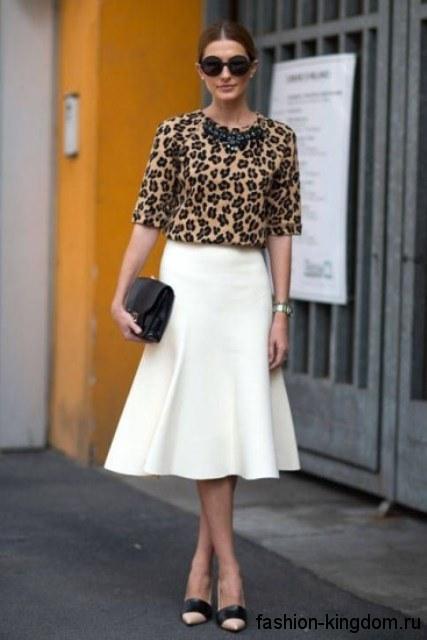 Белая юбка-миди трапециевидного фасона в тандеме с блузкой леопардовой расцветки с рукавами до локтей.