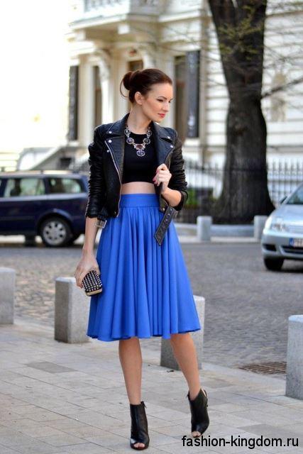 Синяя юбка-миди трапециевидной формы, с высокой талией в тандеме с черным топом и кожаной курткой.