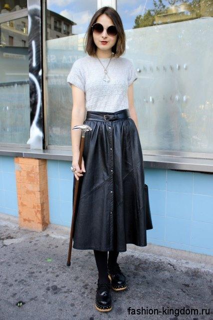 Кожаная юбка-миди свободного кроя, черного цвета, с пуговицами и ремешком в тандеме с серой футболкой.