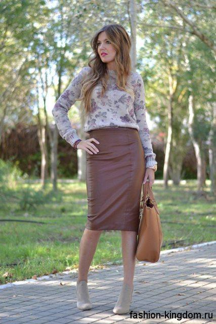 Кожаная юбка-миди шоколадного цвета, узкого фасона в тандеме с серой блузой с цветочным принтом.