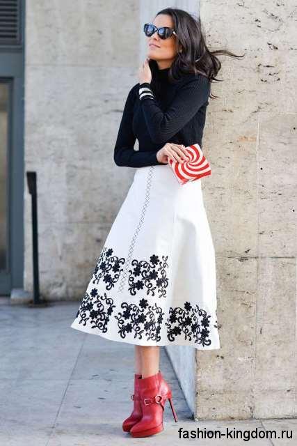 Белая юбка-миди с черным принтом, трапециевидного фасона сочетается с черной кофточкой.