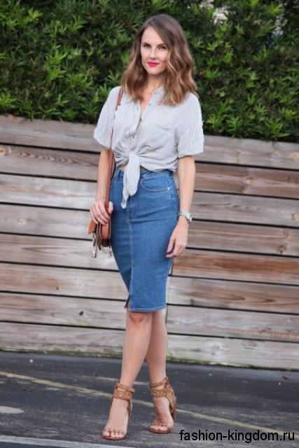 Джинсовая юбка-миди синего цвета, узкого покроя в сочетании с короткой серой блузкой.