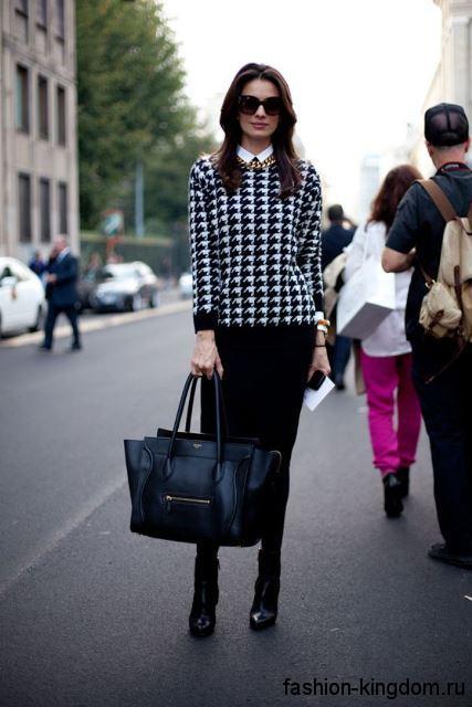 Черная офисная юбка-миди кроя карандаш сочетается с черно-белой кофтой в клетку.