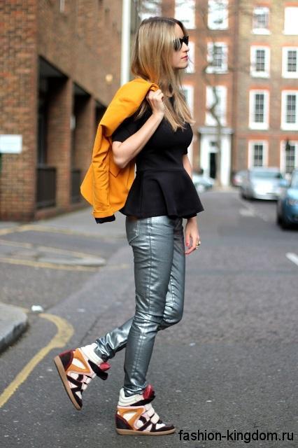 Сникерсы бело-коричневой расцветки, на платформе дополняют узкие брюки серебристого тона и черную блузку.