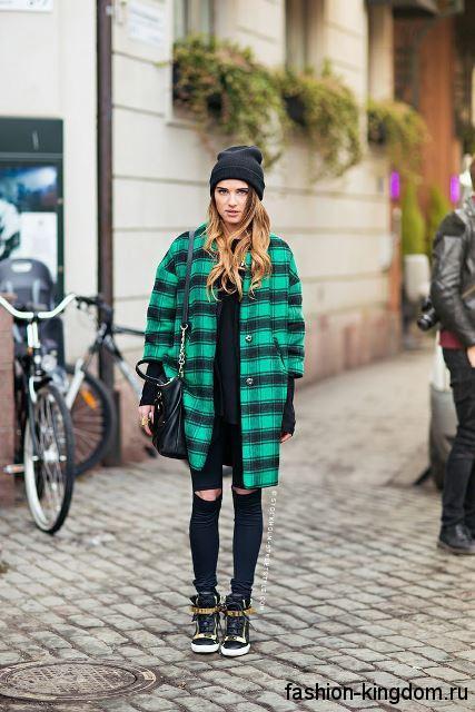 Кожаные сникерсы черного цвета с золотистыми ремешками и шнуровкой сочетаются с пальто черно-зеленого тона в клетку.