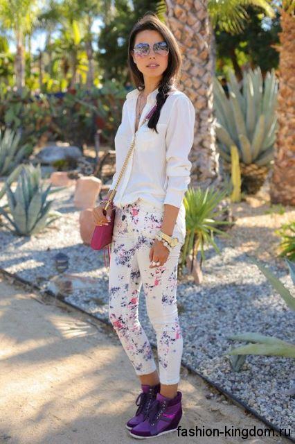 Женские сникерсы фиолетового цвета, на платформе, со шнуровкой в сочетании с белыми брюками с цветочным принтом.