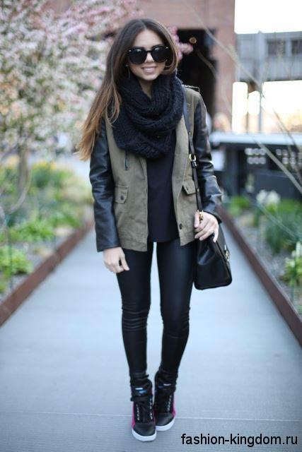 Сникерсы на платформе черного цвета в сочетании с узкими черными брюками и короткой курткой с кожаными рукавами.