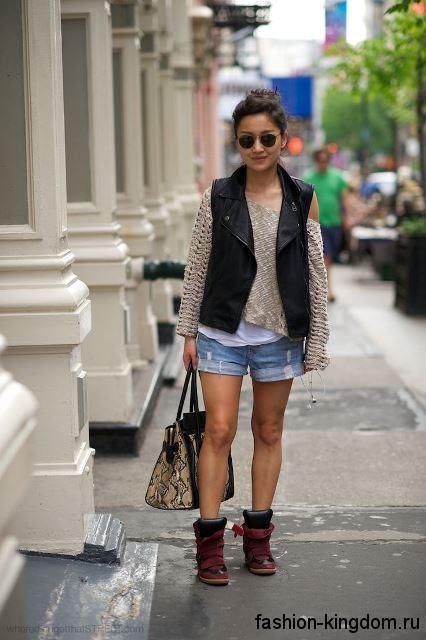 Массивные сникерсы черно-красного цвета на липучке в сочетании с джинсовыми шортами и кожаной жилеткой.