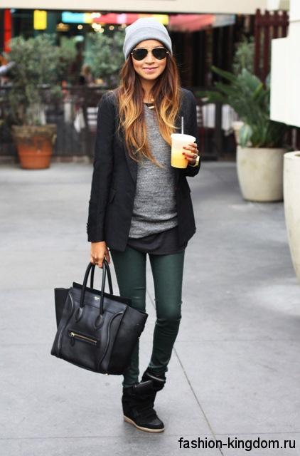 Осенние сникерсы черного цвета сочетаются с черным пиджаком и узкими брюками темно-зеленого тона.