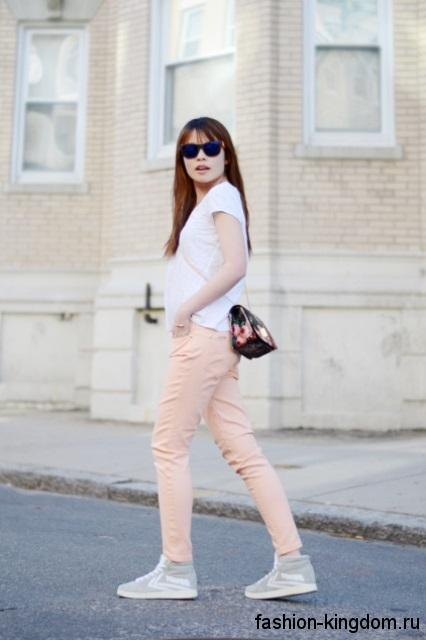 Летние сникерсы серого цвета с белыми вставками дополняют узкие брюки персикового тона и белую футболку.