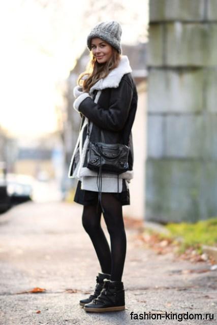 Кожаные сникерсы черного цвета на липучке сочетаются с короткой зимней курткой черного тона.