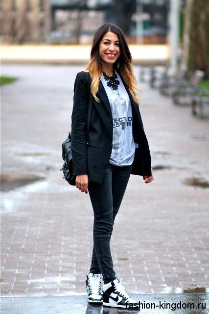 Сникерсы черно-белой расцветки на шнуровке сочетаются с черными джинсами и пиджаком.