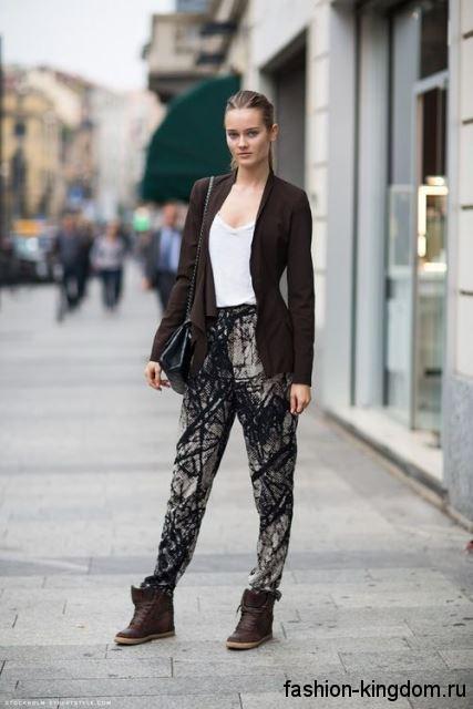 Осенние сникерсы шоколадного цвета, на шнуровке сочетаются с брюками черно-серой расцветки и коричневым кардиганом.