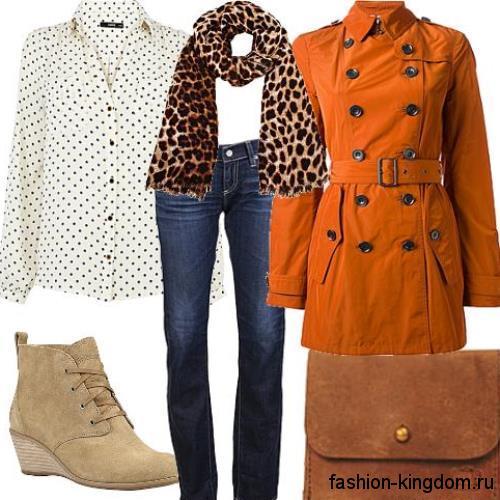 Тренчкот оранжевого цвета, прямого силуэта с широким пояском в сочетании с синими джинсами и белой блузкой в горошек.