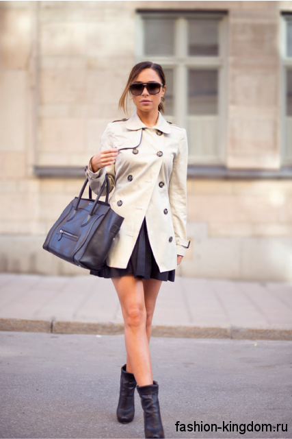 Короткий тренчкот белого цвета, приталенного покроя сочетается с кожаными черными ботильонами на каблуке.
