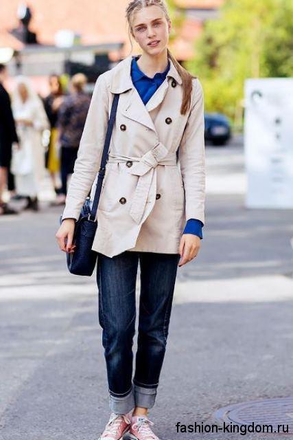 Тренчкот белого цвета с пояском, средней длины в сочетании с прямыми джинсами и кедами.