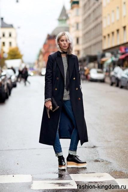 Длинный тренчкот темно-синего цвета, трапециевидного фасона сочетается с узкими синими джинсами.