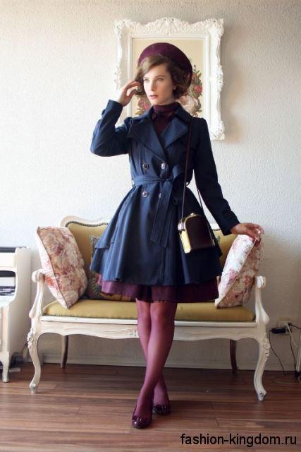 Женский тренчкот темно-синего цвета, с пышным низом, длиной выше колен в сочетании с туфлями на каблуке.