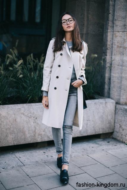Белый тренчкот прямого покроя, длиной до колен сочетается с серыми джинсами и кожаными черными туфлями.