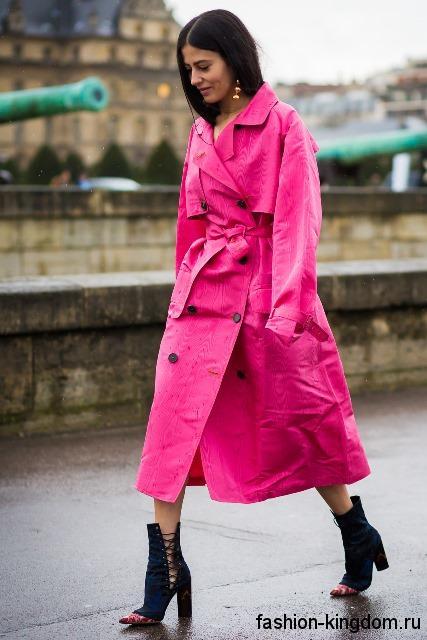Длинный тренчкот розового цвета, свободного покроя, с пояском в тандеме с открыми сапогами на каблуке.