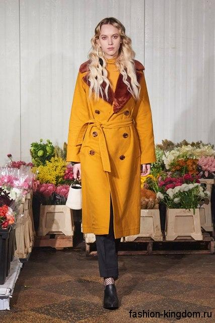 Осенний тренчкот горчичного цвета, прямого покроя, длиной ниже колен, с поясом и меховым воротником от Simon Miller.
