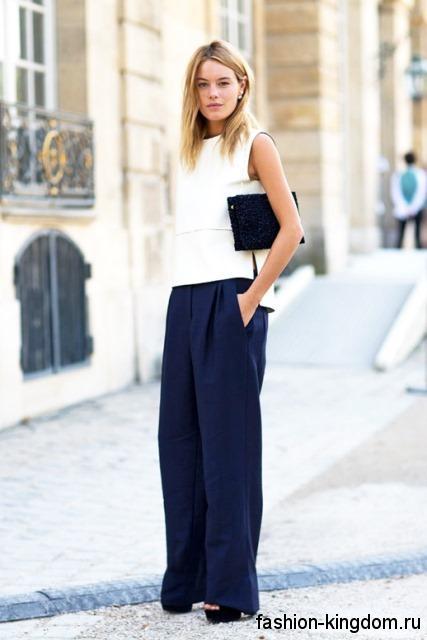 Классическая белая блузка прямого покроя, без рукавов сочетается с широкими брюками темно-синего тона.