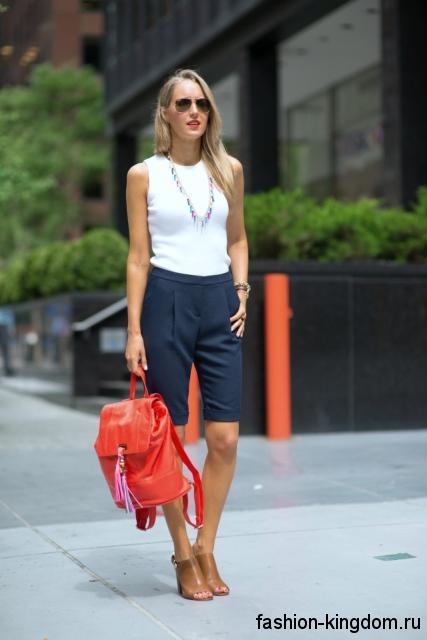 Красный рюкзак коричневые туфли дополняют черные бриджи классического фасона и белую блузку без рукавов.