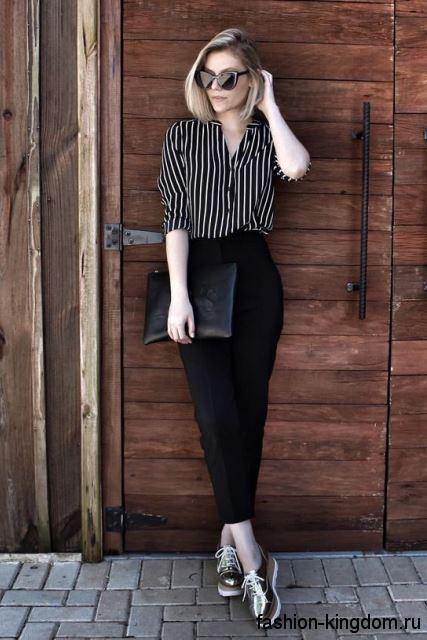 Классическая блузка черно-белого цвета в полоску в сочетании с укороченными черными брюками.