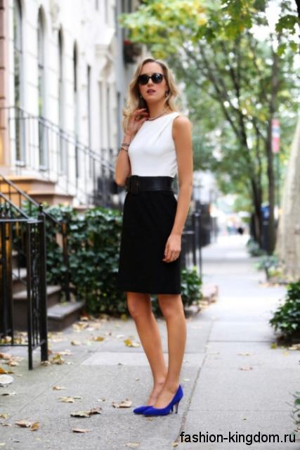 Черная юбка-карандаш с широким поясом сочетается с классической белой блузой без рукавов и синими туфлями на каблуке.