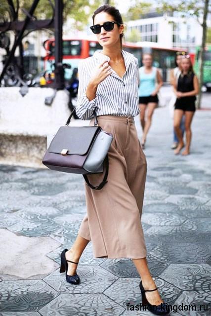 Сумочка серых оттенков и черные туфли сочетаются с широкими укороченными брюками бежевого цвета и черно-белой блузой.