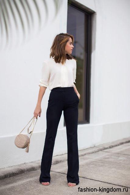 Черные брюки классического фасона сочетаются с блузкой белого цвета, свободного покроя.