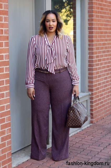 Классические брюки темно-фиолетового цвета, с тонким пояском в сочетании с полосатой блузой бело-сиреневого тона.