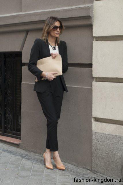 Сумочка-клатч и туфли бежевого цвета сочетаются с классическим брючным костюмом черного тона и белой блузкой.