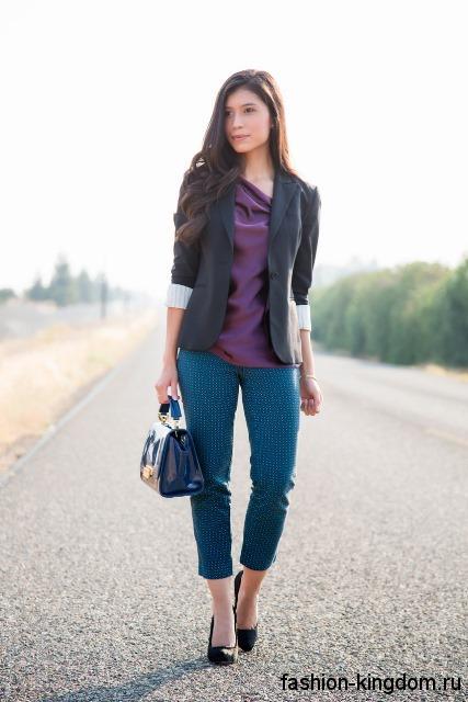 Классический черный пиджак с рукавами до локтей в сочетании с фиолетовой блузой и короткими синими брюками.