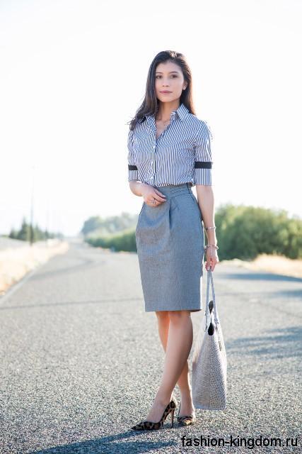 Серая юбка-карандаш классической длины до колен в сочетании с блузкой черно-белого тона в полоску, с рукавами до локтей.