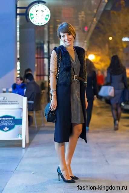 Классические черные туфли и сумочка черного цвета дополняют черное пальто без рукавов и серое платье-миди.