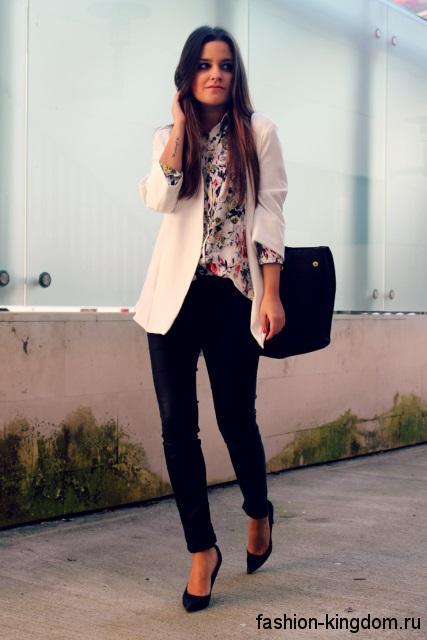 Узкие черные брюки сочетаются с белой блузкой с цветочным принтом и классическим белым пиджаком.