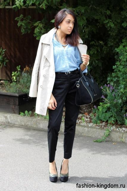 Классические черные брюки в сочетании с голубой блузкой и плащом белого цвета, средней длины.