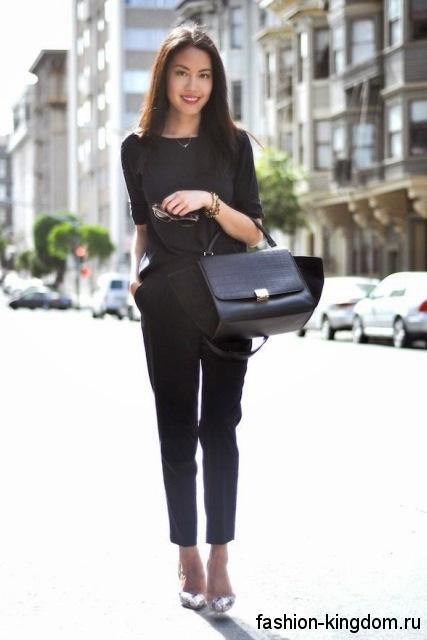 Классические брюки черного цвета сочетаются с черной блузкой с рукавами до локтей и серебристыми туфлями на каблуке.