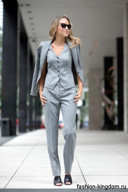 Классический костюм в виде брюк, жилетки и пиджака светло-серого цвета в сочетании с открытыми черными туфлями.
